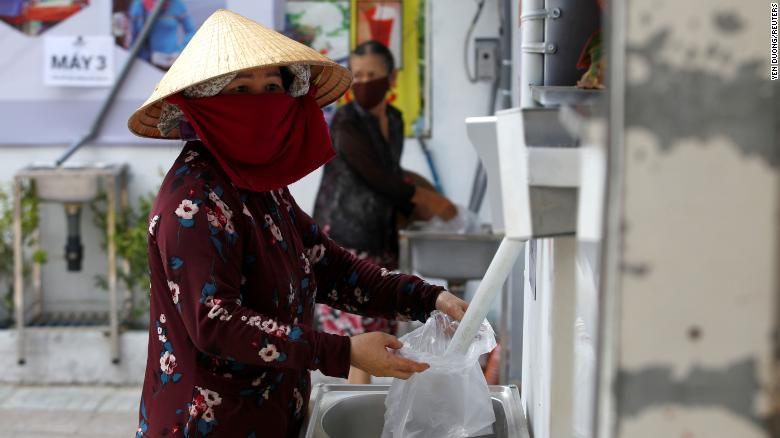 A woman fills a plastic bag with rice from a 24/7 automatic rice dispensing machine in Ho Chi Minh City, Vietnam, on April 11, 2020. Image: Reuters