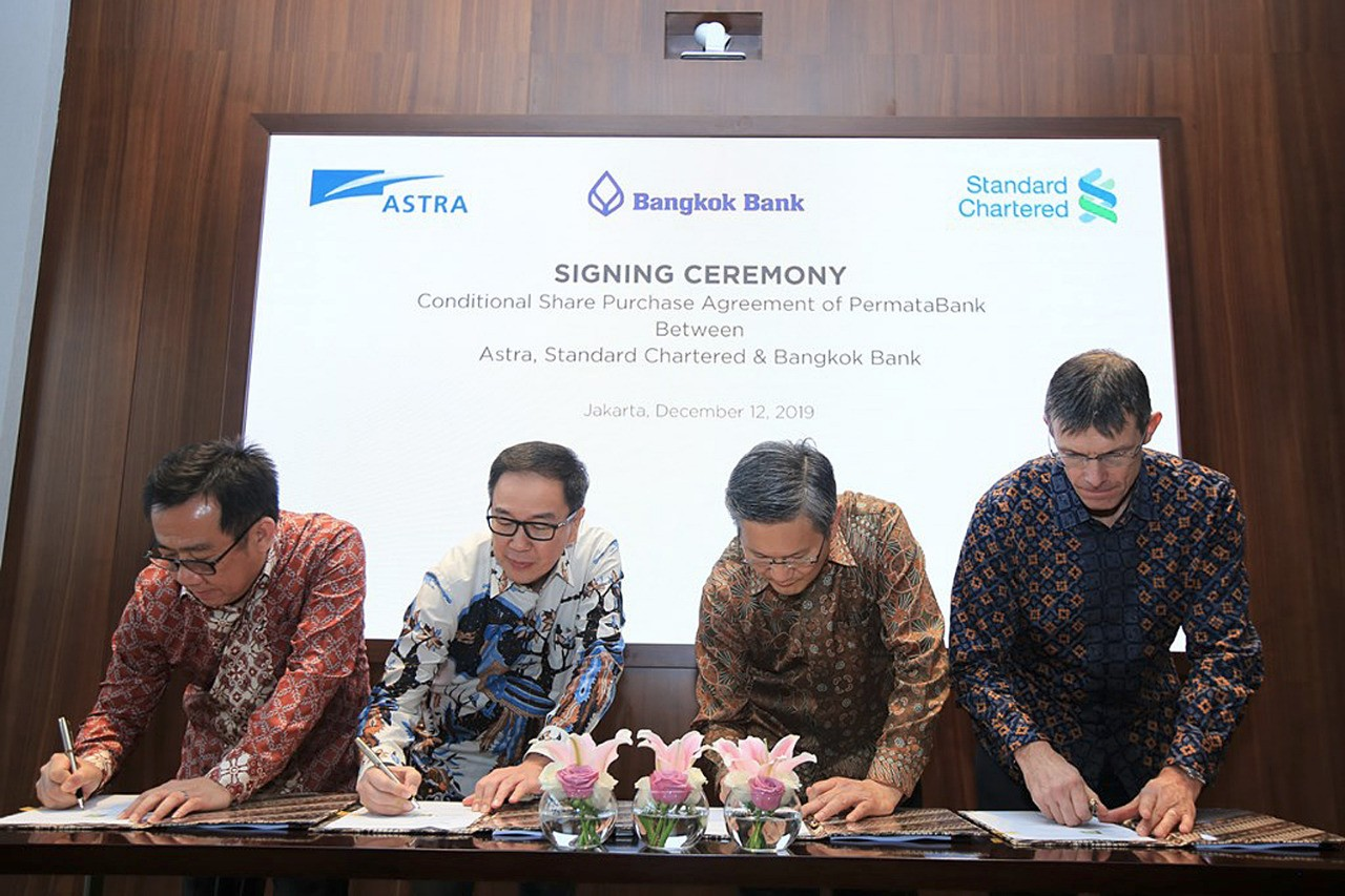 Signed and sold: Bangkok Bank president Chartsiri Sophonpanich (second right), Astra International president director Prijono Sugiarto (second left), Standard Chartered corporate development group head David Churchman (right) and Astra vice president director Djony Bunarto Tjondro sign conditional sale and purchase agreements on Bangkok Bank's acquisition of 89.12 percent of Bank Permata's shares from Astra and Standard Chartered in Jakarta on Thursday (12/12/19). Image: Antara/Hama