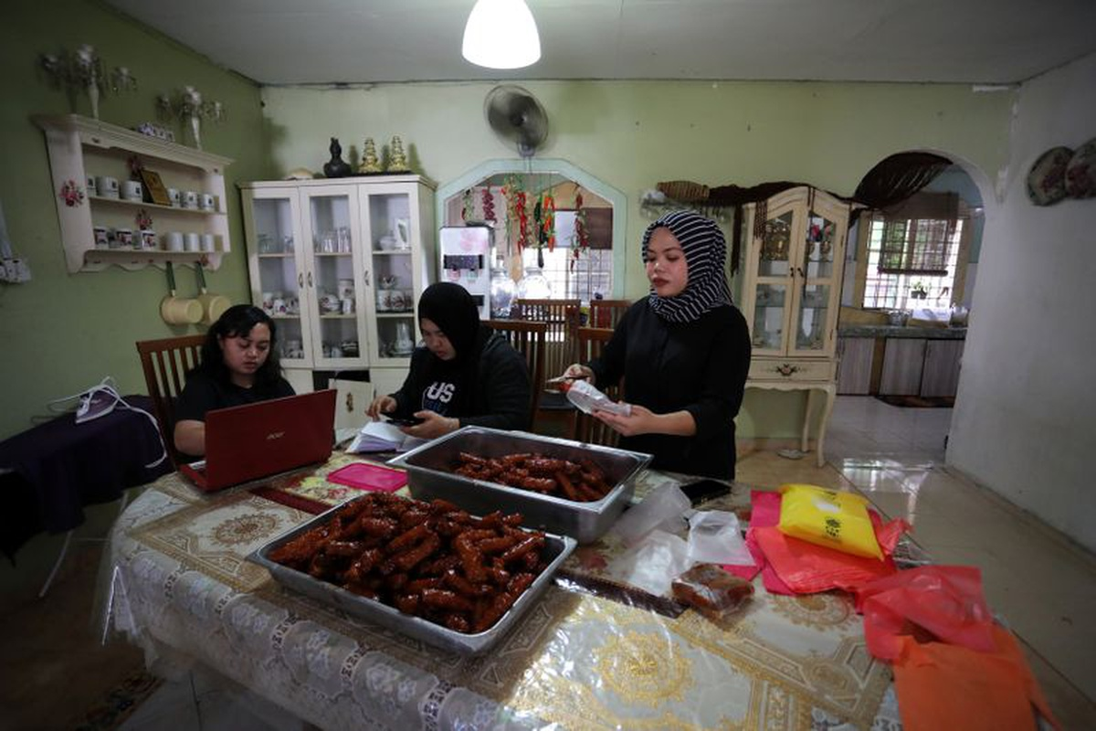 "Online Ramadan bazaar trader Nur Shaheera Mohd Sabri packs ""Popiah"" spring rolls, while her family members check online orders at her home, during the movement control order due to the outbreak of the coronavirus disease (COVID-19), in Sungai Buloh, Malaysia April 11, 2020. Picture taken April 11, 2020. Image: REUTERS/Lim Huey Teng"