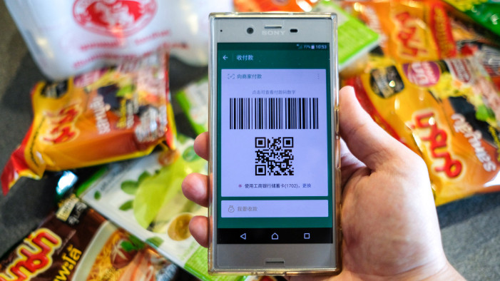 A Chinese customer prepares to pay with Wechat in Bangkok, Thailand on May 5, 2017. Image: XINHUA/LI MANGMANG VIA GETTY IMAGES