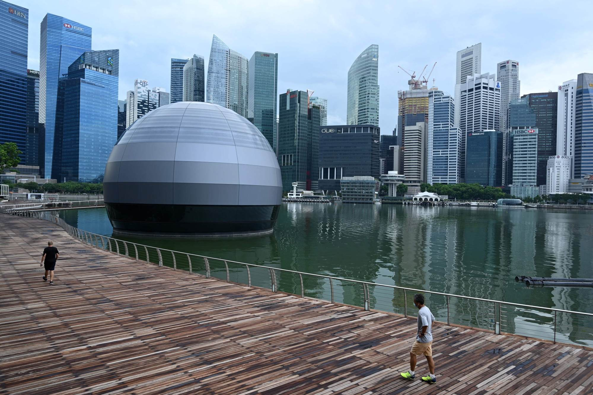 People wearing face masks walk along the promenade at Marina Bay in Singapore on May 4. Image: Roslan Rahman/AFP via Getty Images