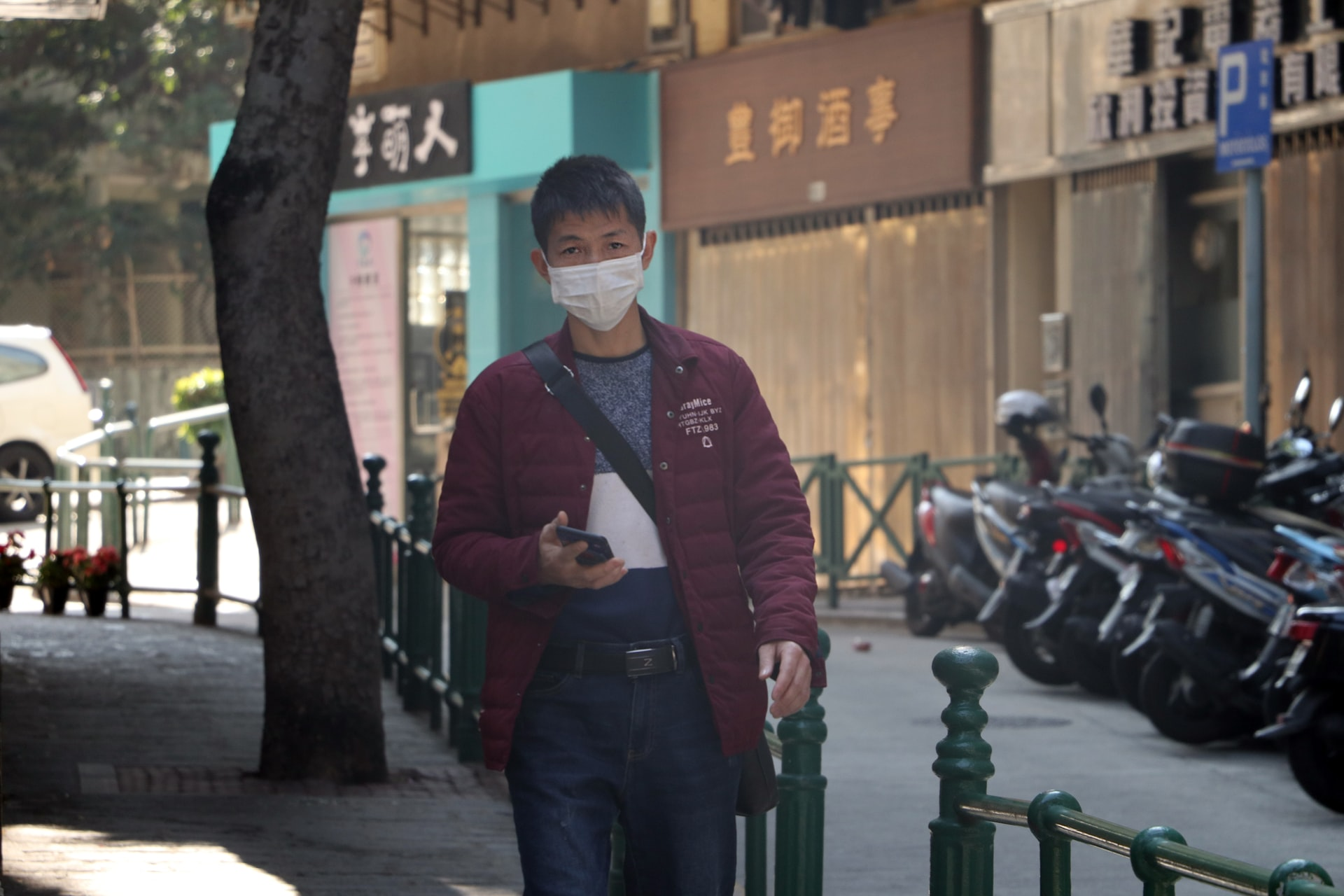 A man walks on the street in Macau, China wearing a protective mask to prevent infection by the coronavirus.Image: Macau Photo Agency on Unsplash