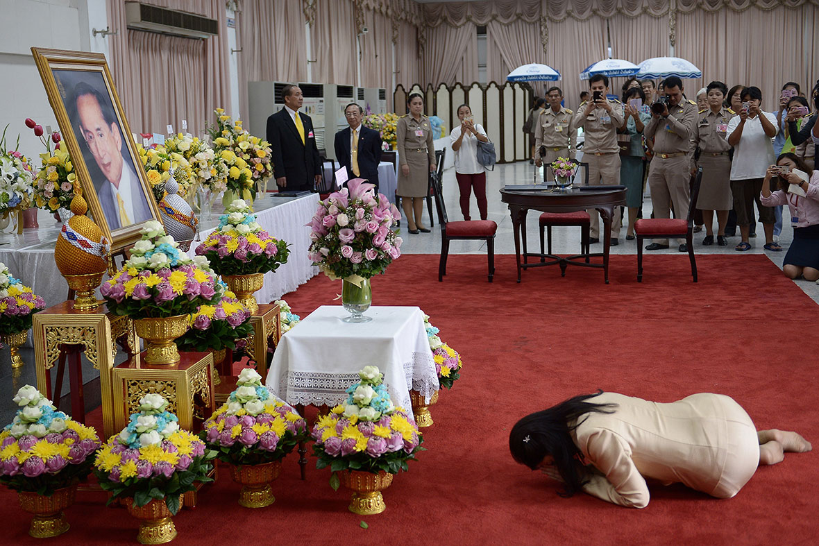 Ex Thai prime minister, Yingluck Shinawatra kneels down in front of a portrait of Thai King Bhumibol Adulyadej as she pays her respects during a visit at the Siriraj hospital in Bangkok (babaimage.com)
