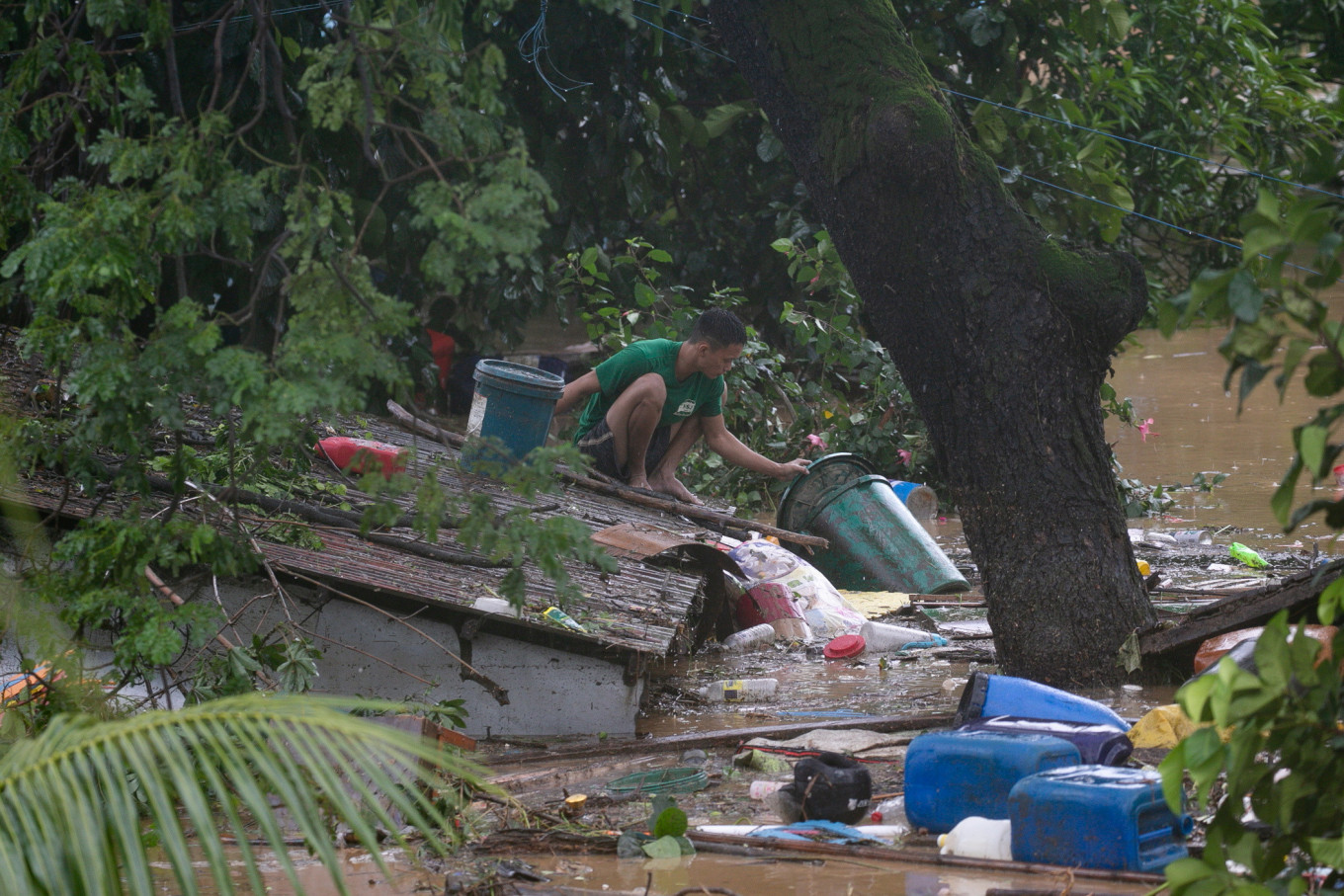 A man retrieves items from a roof, following floods caused by Typhoon Vamco, in San Mateo, Rizal province, Philippines, Thursday (Reuters/Eloisa Lopez)
